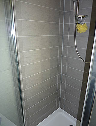 Shower cubicle finished in grey porcelain, contemporary design