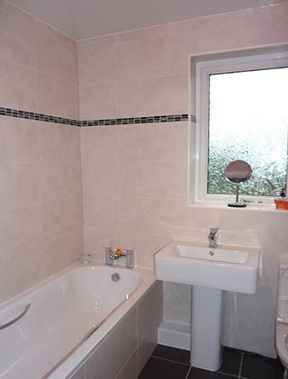 Ceramic wall tiles with black mosaic border, bathh and sink