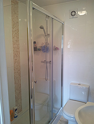 Shower cubicle finished in white ceramic wall tiles and travertine mosaic vertical column