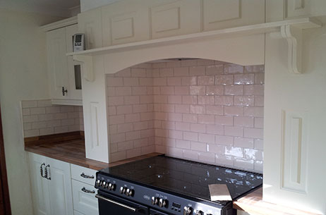 White kitchen wall tiles fitted in brick style layout, they have been finished with white grout
