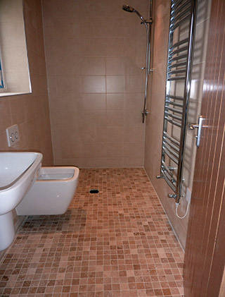 Wetroom with travertine mosaic floor tiles and ceramic beige wall tiles