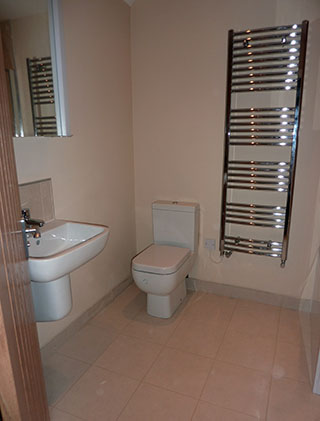 Bathroom with beige fllor tiles white utilities and chrome towel radiator