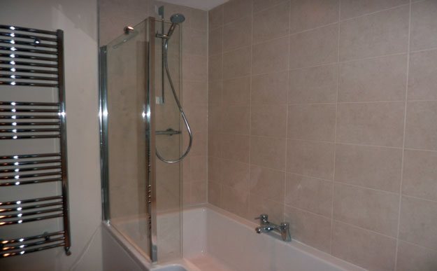 Bathroom with beige wall tiles chrome towel radiator and bath shower screen