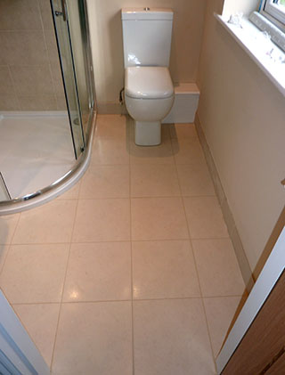 Ensuite bathroom with beige wall and floor tiles white utilities