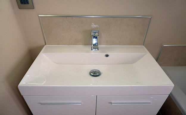 White modern bathroom sink with beige tiles and aluminium trim