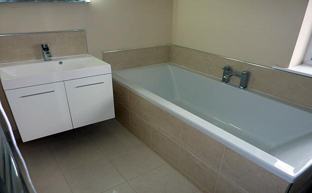 Ensuite Bathroom With Beige Tiles On Floor, Bath Panel , Bath Splash Back  And